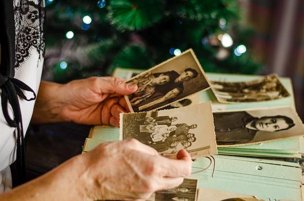 Женские руки держатся и старые фото ее родственников Premium Фотографии