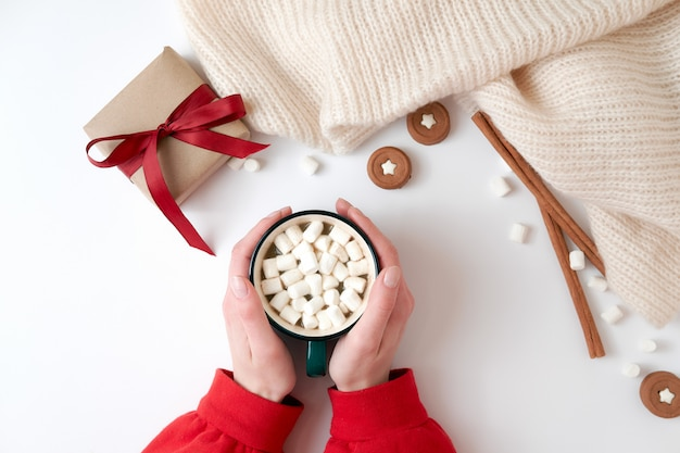 Female hands holding cup of hot chocolate with marshmallow Premium Photo