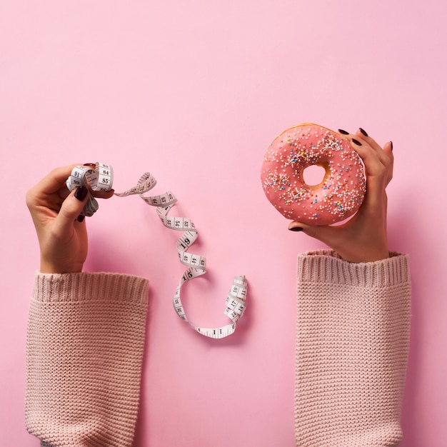 Female hands holding donut and measuring tape over pink background Premium Photo