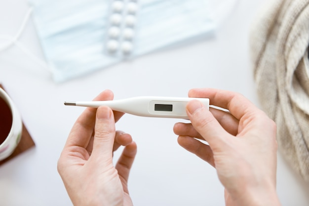 Female hands holding electronic thermometer over the white offic Free Photo