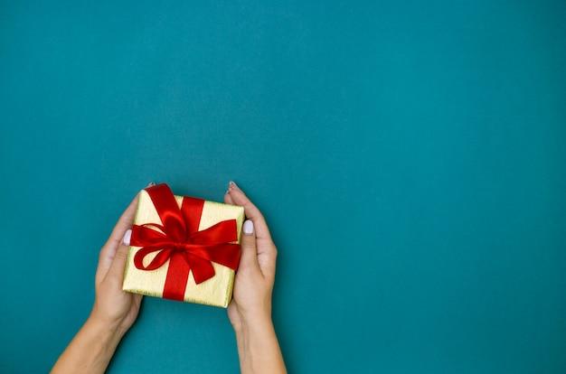 파란색 배경에 선물을 들고 여성 손 무료 사진