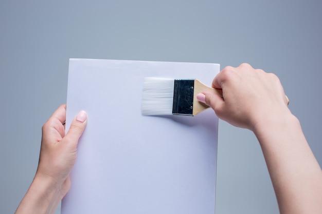 Женские руки держат кисть на белом холсте Бесплатные Фотографии