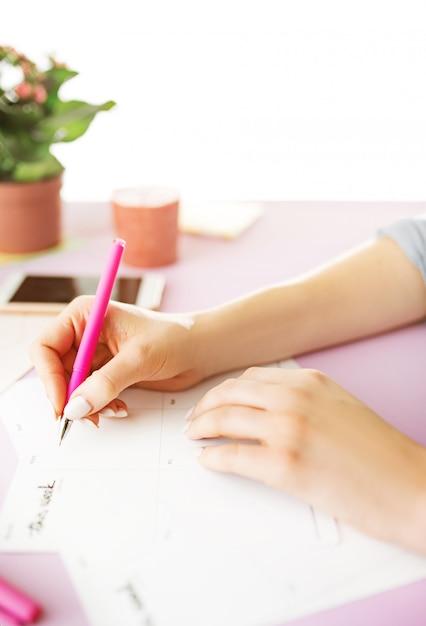 ペンを持つ女性の手。トレンディなピンクの机の上の電話。 無料写真