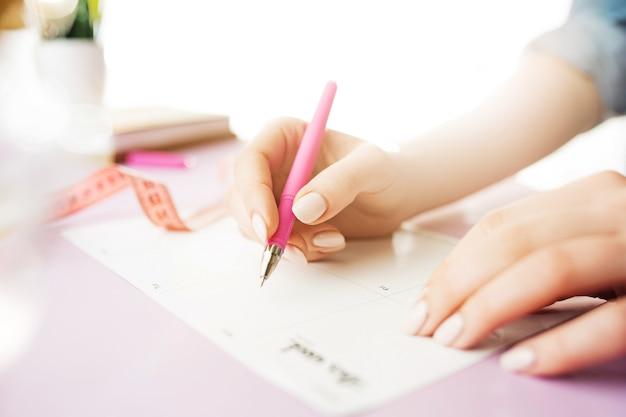 ペンを持つ女性の手。トレンディなピンクのデスク。 無料写真