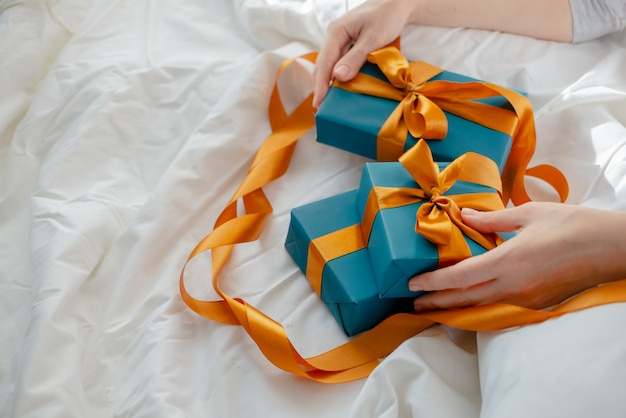 Female hands holding presents bedside. new year and christmas concept. top horizontal view. Premium Photo