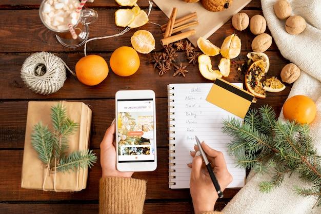 休日の前にオンラインショップで購入する女性の手がスマートフォンを持ち、クリスマスプレゼントのリストを作成 Premium写真
