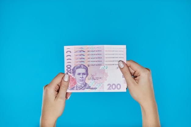 Female hands holding ukrainian banknotes on blue Premium Photo