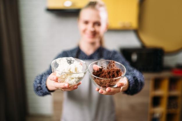 女性の手はチョコレートパウダーとバターを入れたガラスのボウルを保持しています。 Premium写真