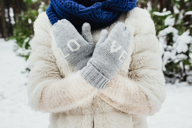 Female hands in knitted mittens. on mittens embroidered with the word love. Free Photo