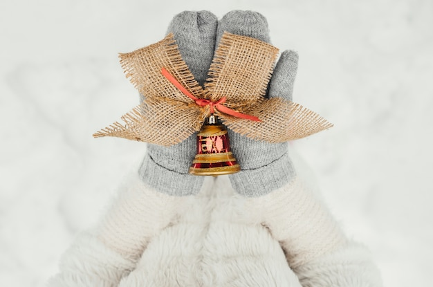 Female hands in knitted mittens with an ornamental bell for christmas decoration Free Photo