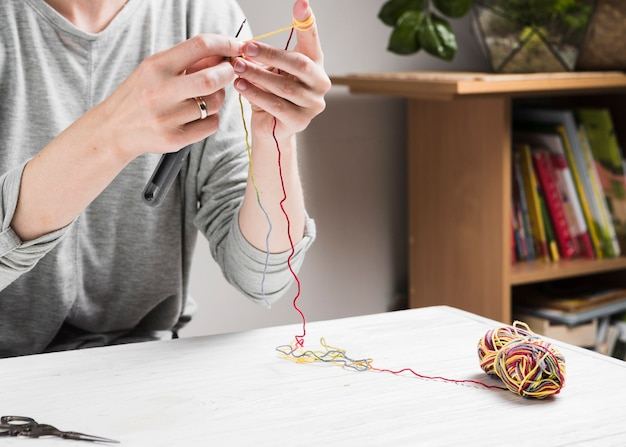 Female hands knitting with colorful thread Free Photo