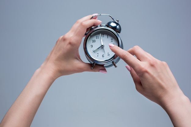 The female hands and old style alarm clock on gray Free Photo