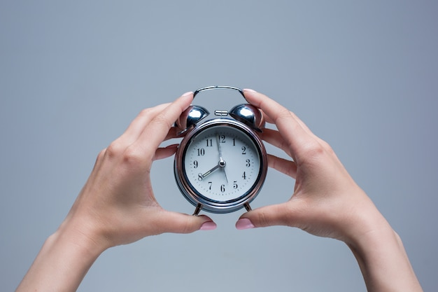 Female hands and old style alarm clock Free Photo