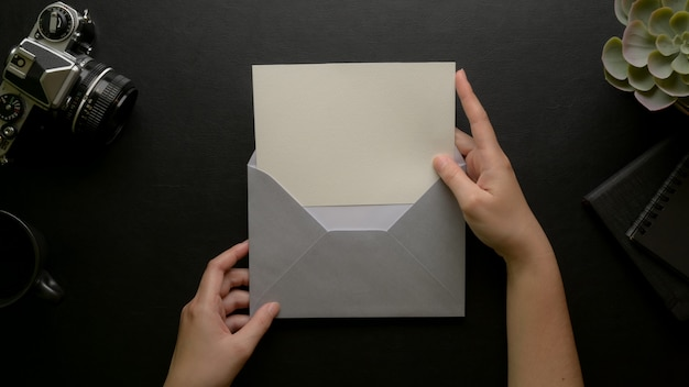 Female hands open greeting card with grey envelope on dark ...