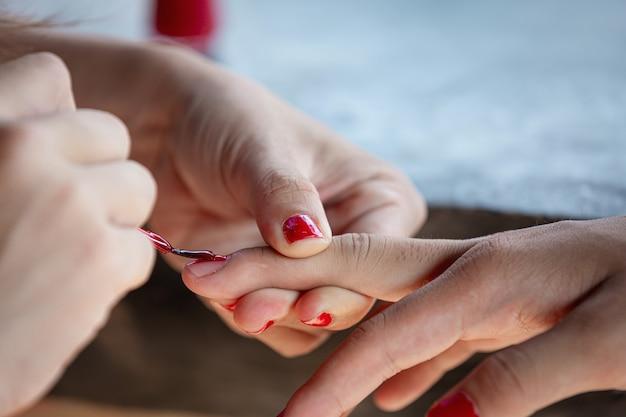 女性の手は赤い光沢で爪を描いた 無料写真