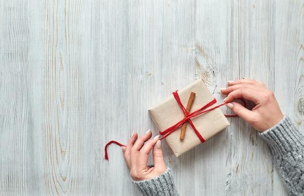 Женские руки готовят рождественские и новогодние подарки для праздничной подарочной упаковки на светлом деревянном столе. подарки родным и близким с поздравлением Premium Фотографии