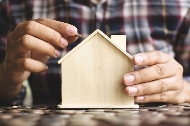 Female hands protection the little wood house model . Premium Photo