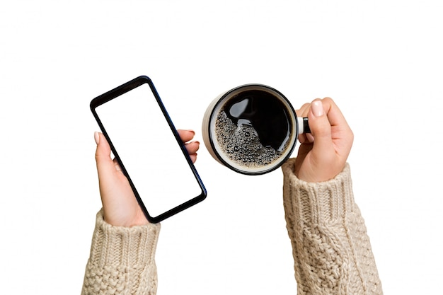 Female hands in sweater touch screen mobile phone with cup of coffee. Premium Photo