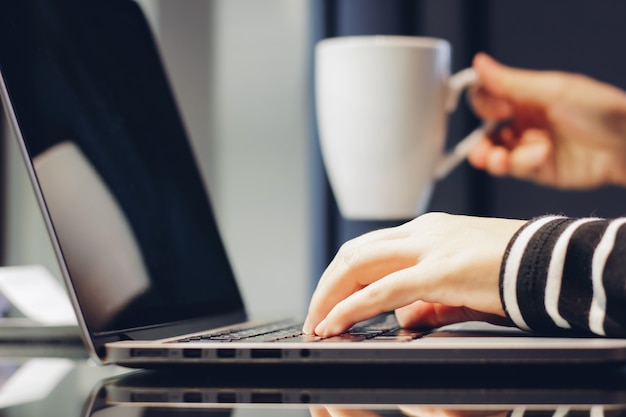 Female hands typing on keyboard of laptop while holding cup of coffee, working at home concept Free Photo