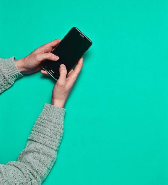Женские руки, используя смартфон на синей поверхности. вид сверху. Premium Фотографии