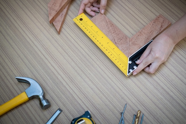 Female hands using a try square to check that the woodworking corners are square with a set collection of working hand tools for the wooden, toolset with the do it yourself (diy) Premium Photo