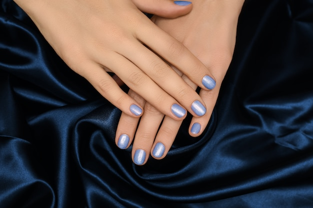 블루 네일 디자인으로 여성 손입니다. 파란색 반짝이 매니큐어 매니큐어. 여자 손에 블루 패브릭 배경 무료 사진