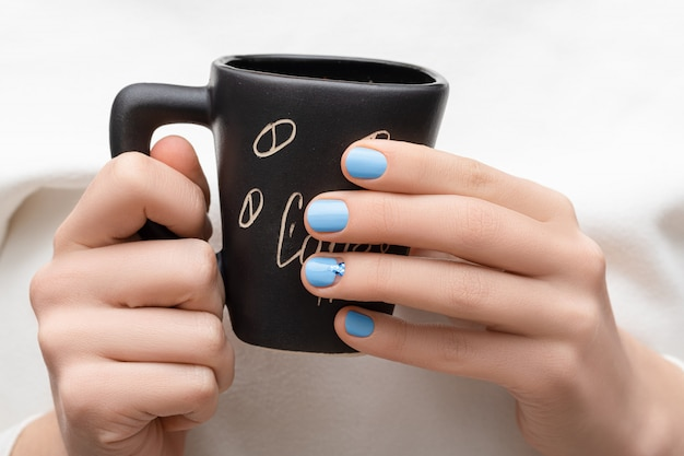 Female hands with blue nail design holding black coffee cup. Free Photo