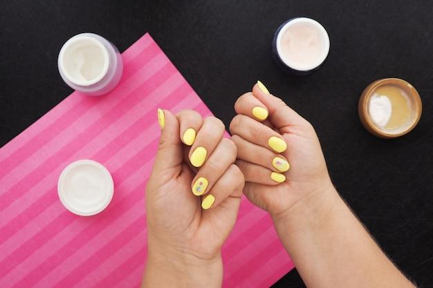 明るい黄色のマニキュアで女性の手。黒いテーブルには、クリーム、ニス、ピンクのナプキンの瓶があります。 Premium写真