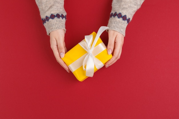 Female hands with christmas gift on red Premium Photo