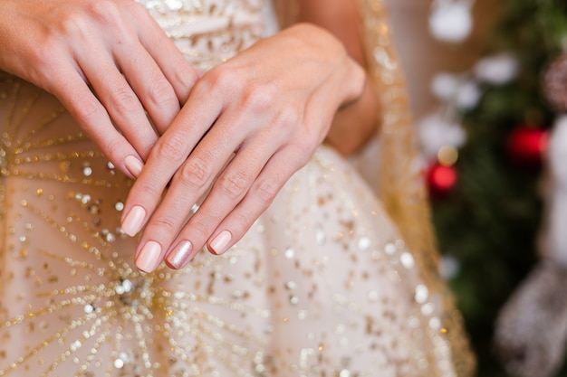 Female hands with christmas new year nail design. nude beige nail polish manicure Free Photo