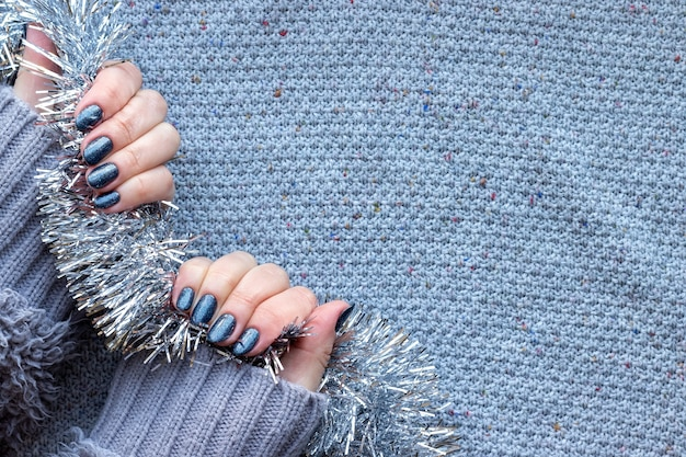 Premium Photo Female Hands With Dark Gray Blue Glittered Nails On Knitted Background With Silver Christmas Tinsel