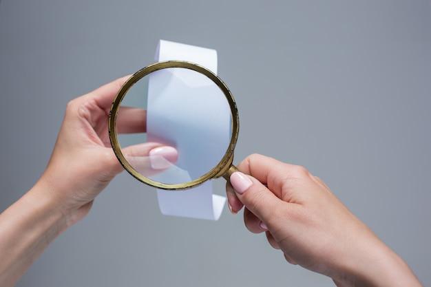 Le mani femminili con carta di transazione vuota o assegno e lente d'ingrandimento Foto Gratuite