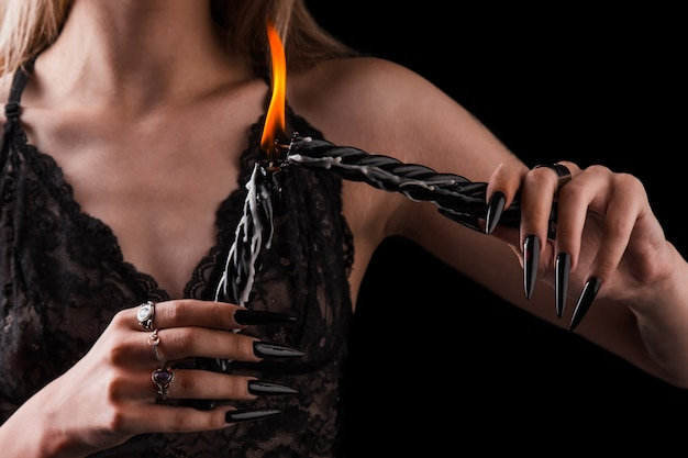 Female hands with long nails hold burning candles, witchcraft on halloween. Premium Photo