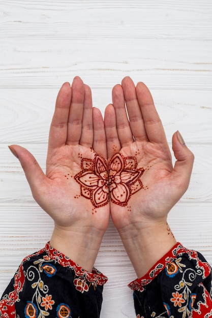 Female hands with mehndi on table Free Photo