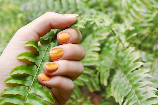 オレンジ色のネイルデザインと女性の手。 Premium写真