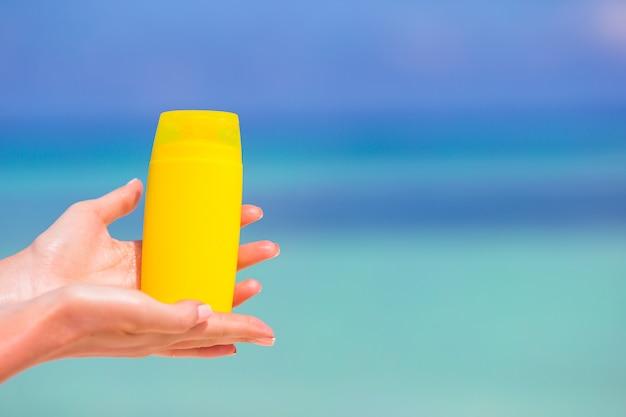 Female hands with suncream bottle blue sea Premium Photo