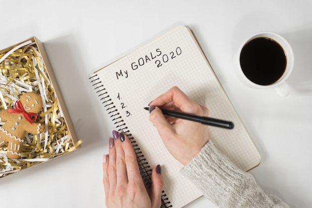 Female hands writing my goals 2020 in a notebook. mug of coffee and gingerbread man, top view Premium Photo