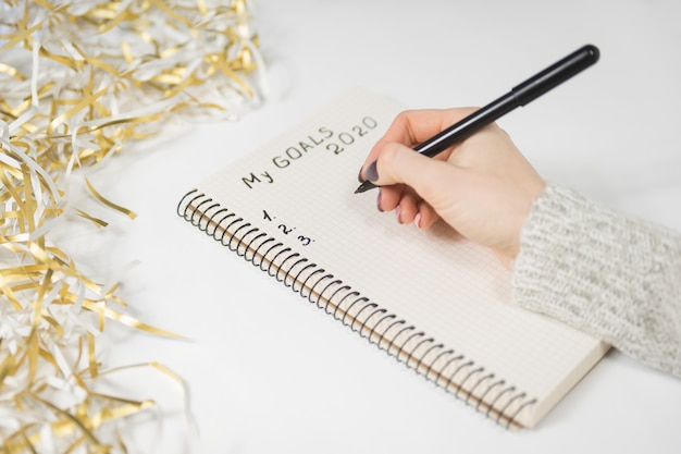 Female hands writing my goals 2020 in a notebook. tinsel, new years concept Premium Photo