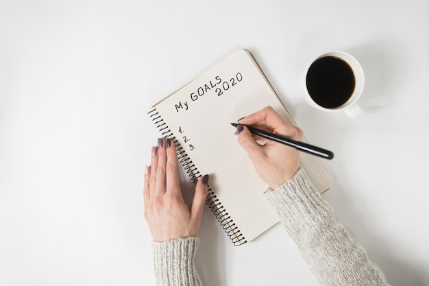 Female hands writing my goals in a notebook. Premium Photo