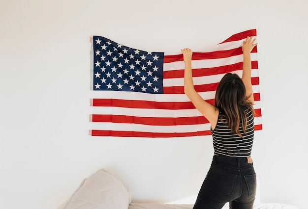 Female hanging national flag on wall Free Photo