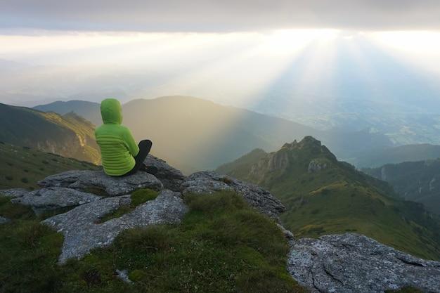 Путешественница, наслаждаясь видом с вершины с солнечными лучами на горизонте Бесплатные Фотографии