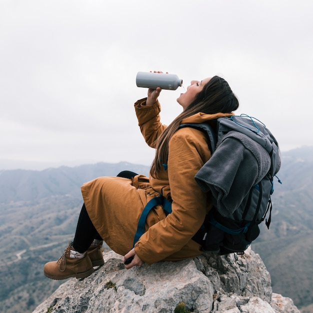A female hiker sitting on top of mountain drinking the water from bottle Free Photo