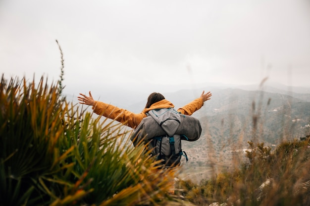 A female hiker with backpack outstretching her arms in mountains Free Photo