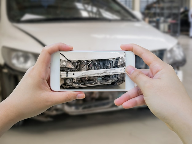 Female hold mobile smartphone photographing car accident for insurance Premium Photo