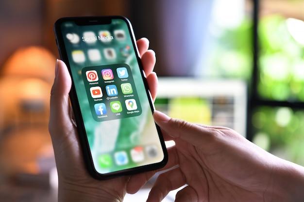 Женщина держит смартфон с иконками социальных медиа на экране у себя дома Premium Фотографии