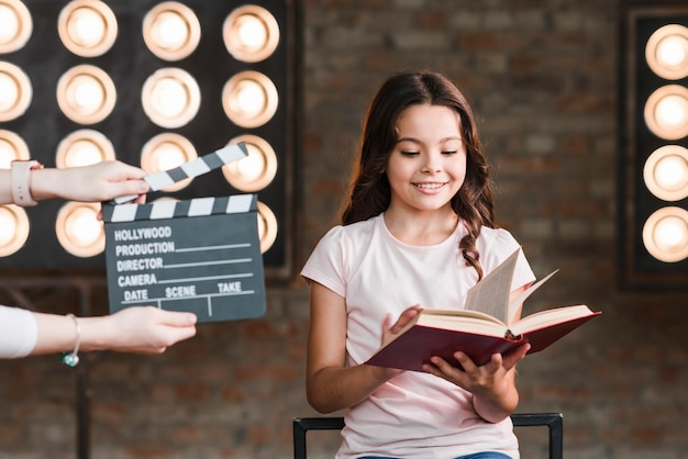 Female holding clapper board in front of girl reading book Free Photo