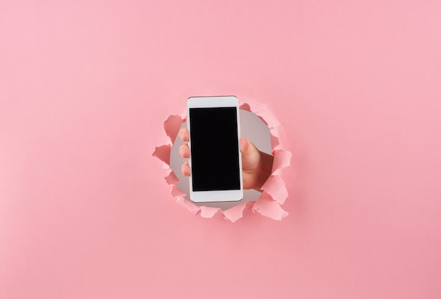 Female holding smartphone in wrapped hole in pink background Premium Photo