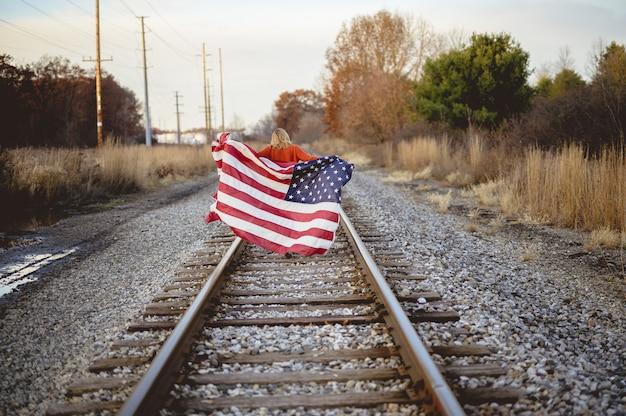Женщина держит американский флаг во время прогулки по железной дороге Бесплатные Фотографии