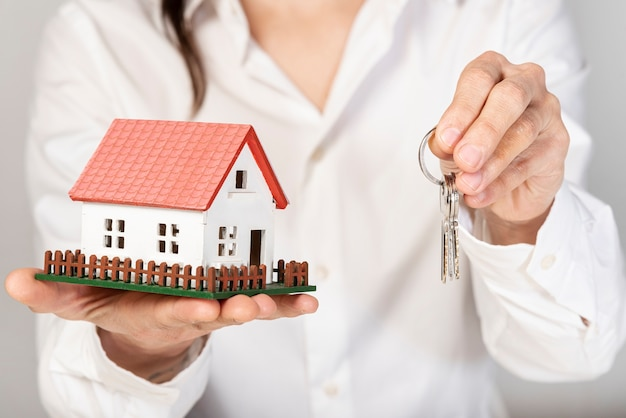 Female holding a toy model house and keys Free Photo