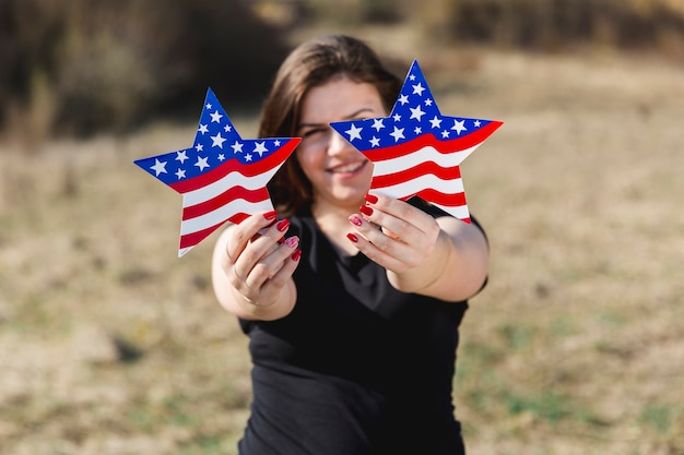 Female holding usa flag stars and looking at camera Free Photo